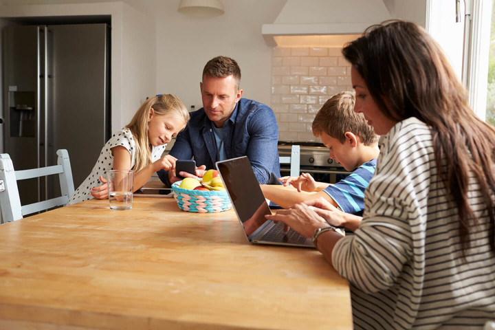 Family at table using gadgets